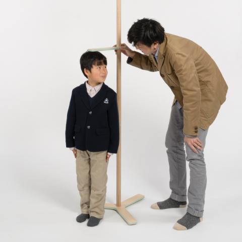 位置を自在に変えられるフックを使い、身長計のように家族で身長を測り、その高さに服をかけることができるコートラック「growth」2