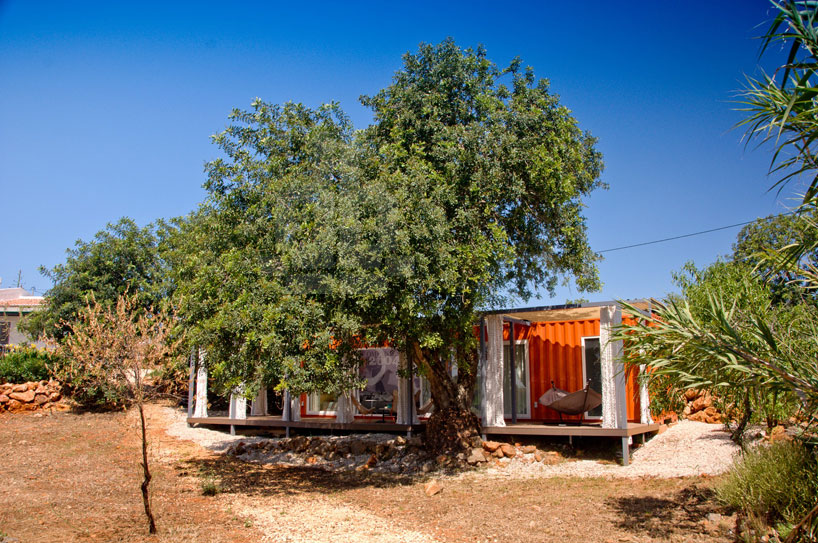 荷物輸送用のコンテナでつくられた、ハンモックのあるオレンジ色のコンテナハウス
