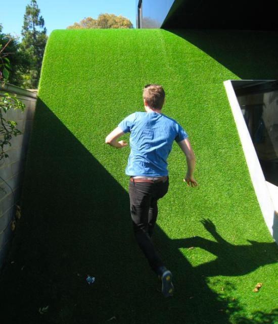 丘の芝生がある家